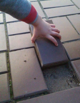 Дете взема и без усилие изважда плочка от уличната настилка, която хлопа Снимка: Мика Сийминеен